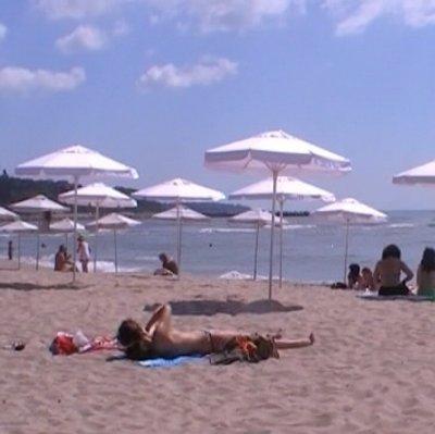 Край на плажа, покрит с платени чадъри