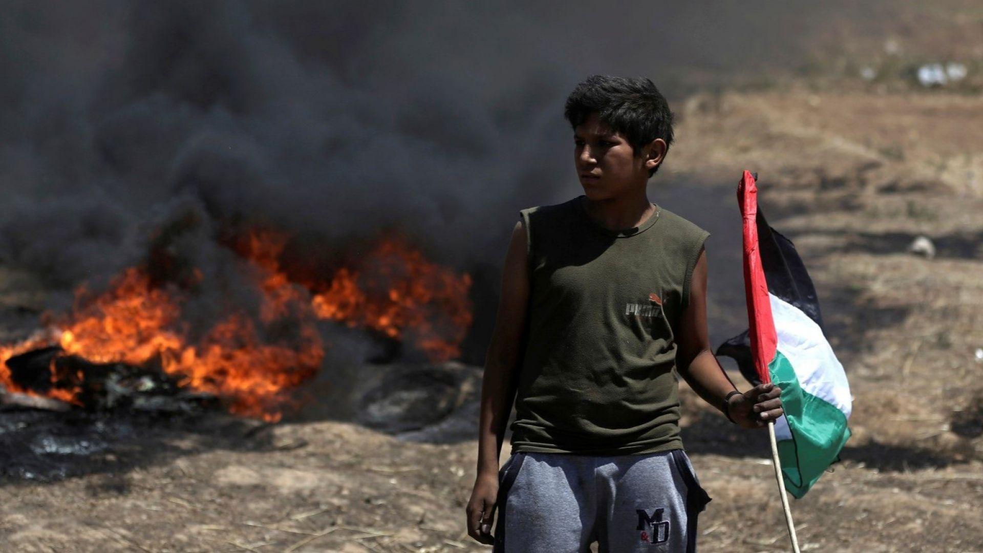 Момче държи палестинския флаг по време на кървавите сблъсъци с израелската армия в ивицата Газа