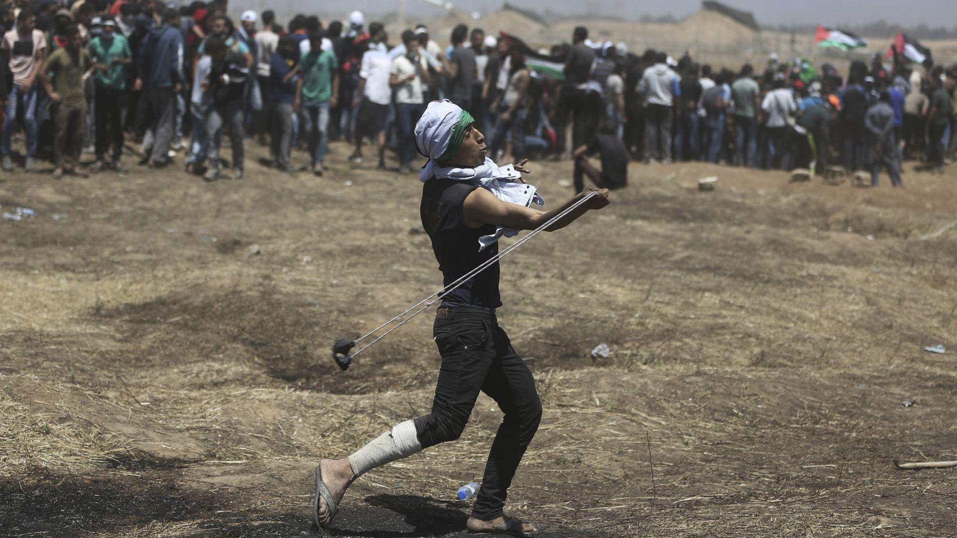 Палестинец хвърля камъни по израелските войнци по време на протеста край границата с Израел