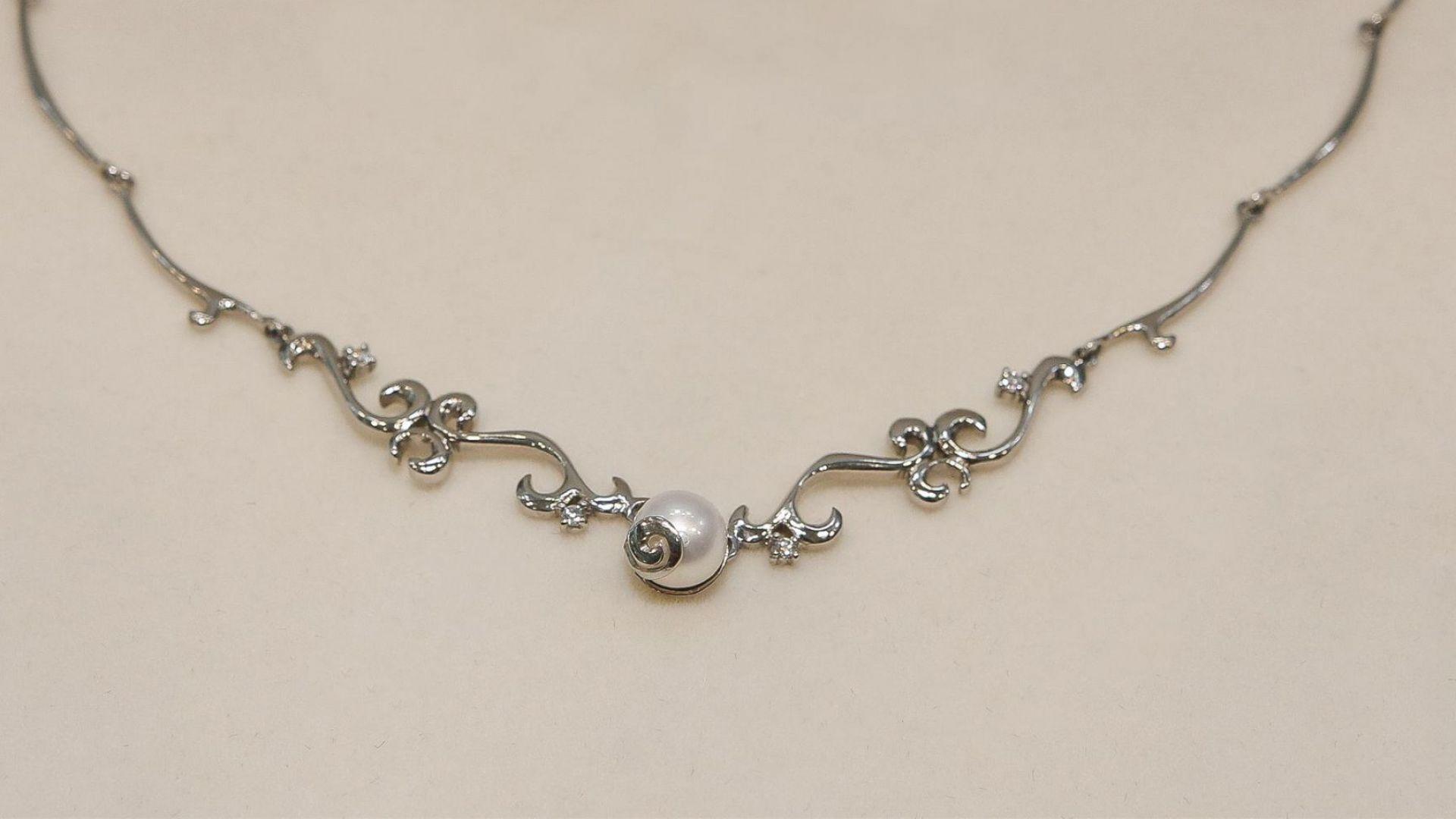 Изящното колие на Goto Jewellery and diamonds е ръчно изработено от бяло злато, перла и четири диаманта