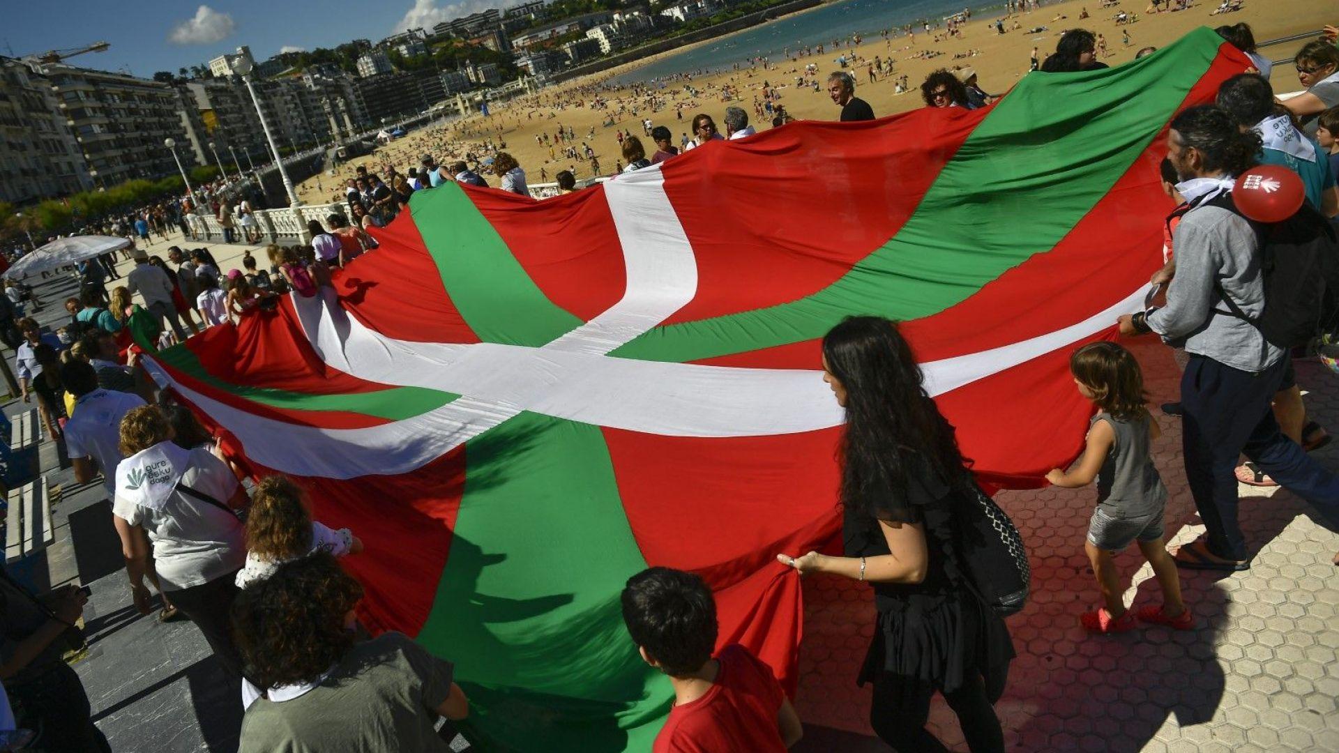 """Демонстрантите държат флага на Страната на баските на плажа """"Ла Конча"""" в Сан Себастиан"""
