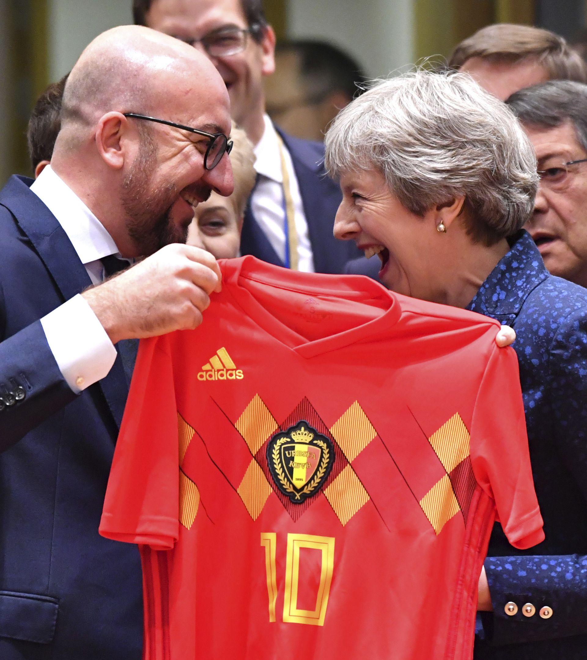 как двамата премиери се смеят, докато Мишел вади фланелка с номер 10 на капитана на Белгия Еден Азар