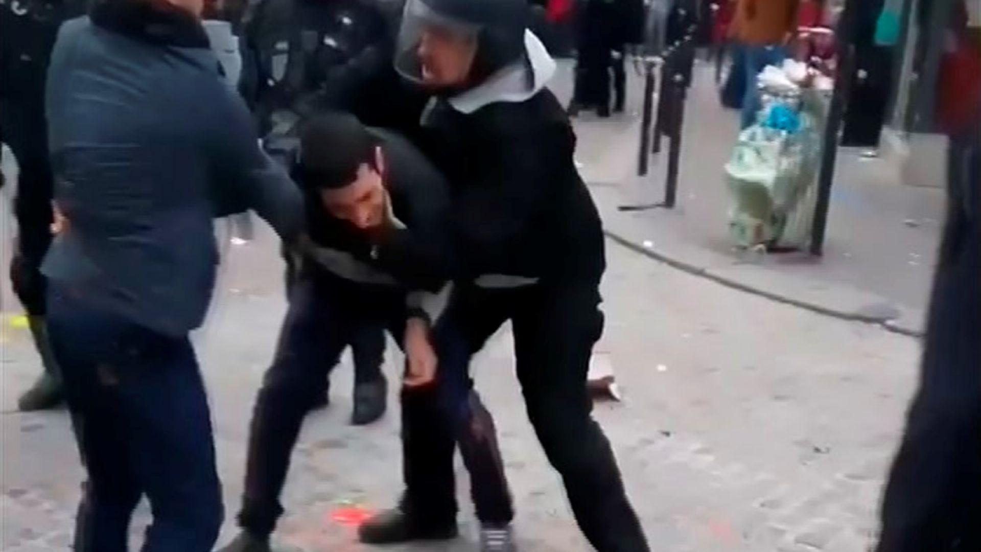 Бенала (вдясно) с полицейска каска бие протестиращ