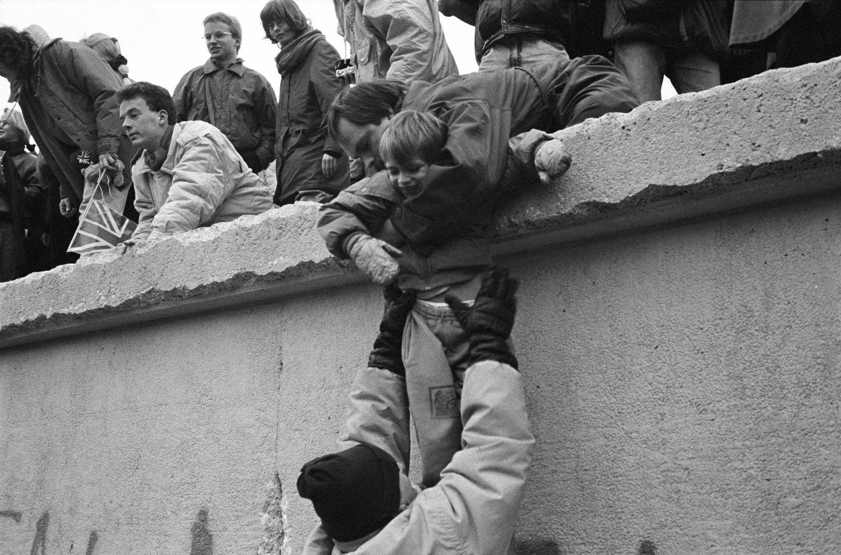 След като стената пада символично, стотици жители на ГДР се катерят по нея
