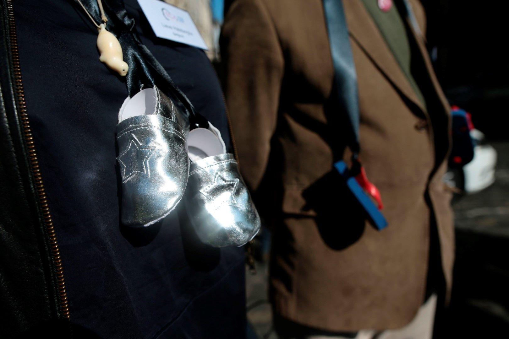 Майки протестираха с бебешки обувки, вързани с черни панделки на шиите им