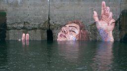 Жени, излизащи от водата, върху бетонните стени на крайбрежието на океана