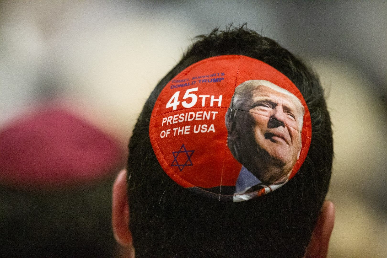 Мъж носи ермолка с лика на Доналд Тръмп по време на възпоменаелната церемония в синагогата