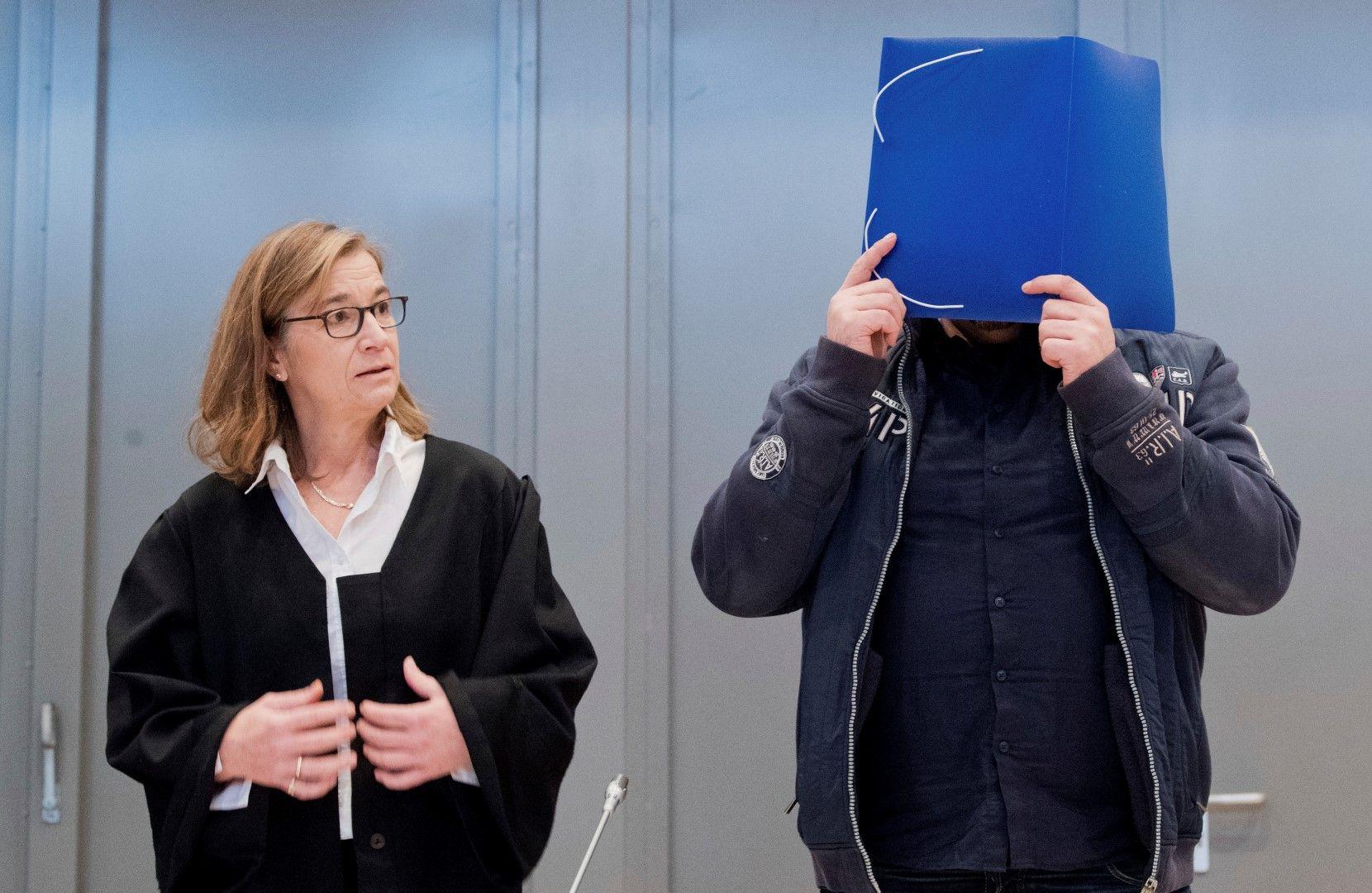 Обвиняемият Хьогел прикрива лицето си пред съда