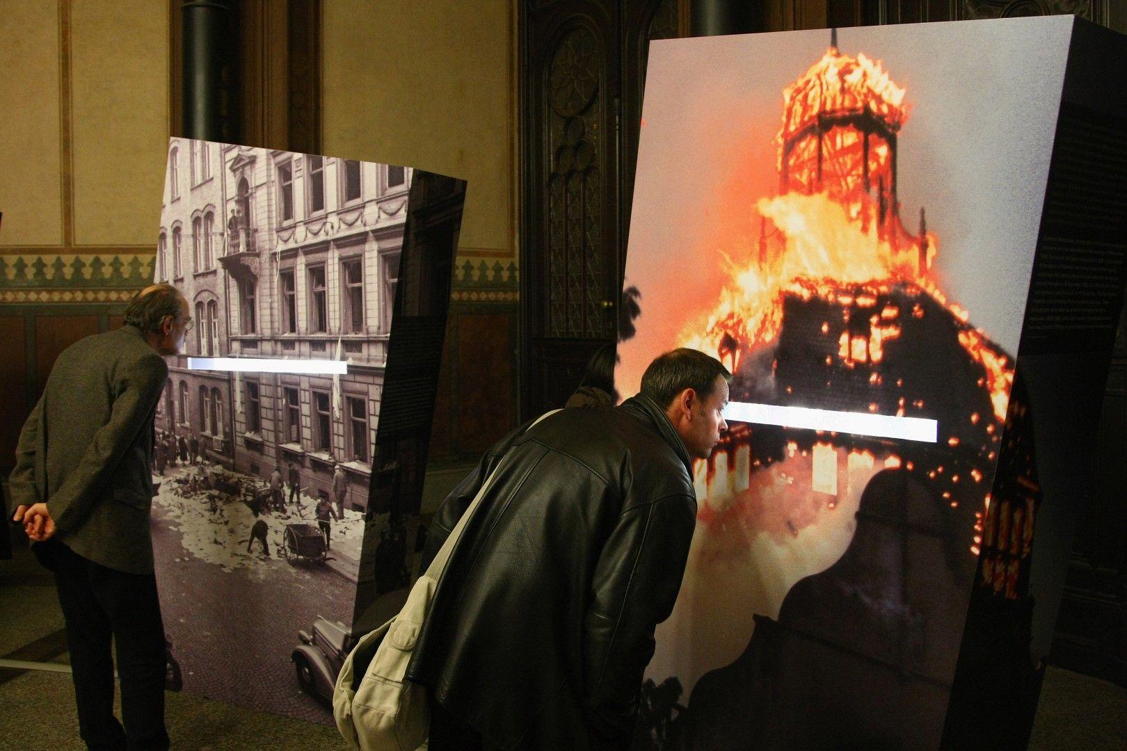 Посетители в германски музей гледат снимки на горяща синагога и други архивни кадри