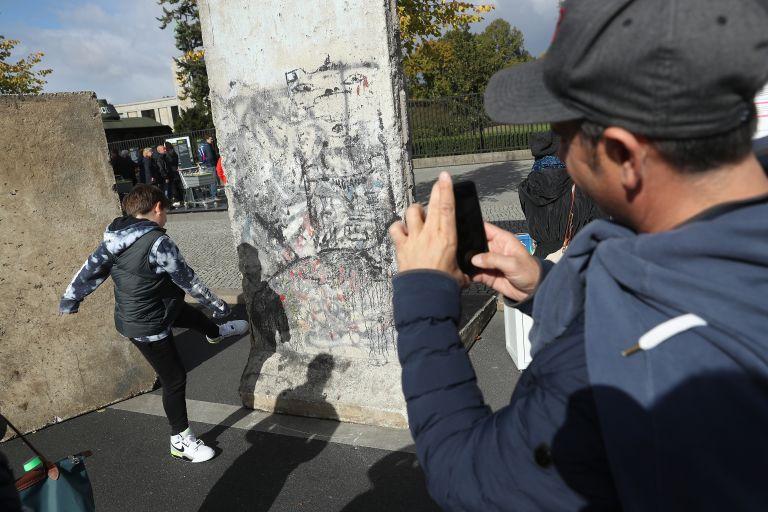 Баща фотографира сина си, който се преструва, че бута Берлинската стена по време на тържествата, отбелязващи деня на немското единство на 3 октомври 2018 г. в Берлин