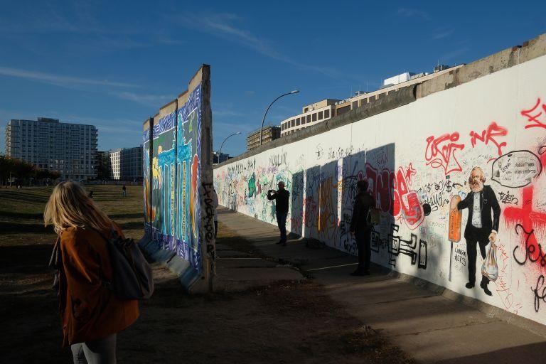 Туристите стоят на бившата част на Берлинската стена, наречена Галерия Ийстбъд