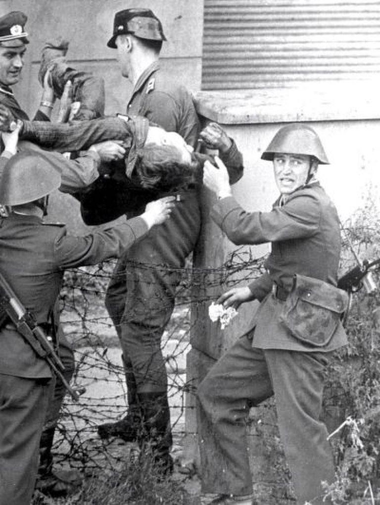 Гранични полицаи носят трупа на Петер Фехтер, застрелян на 17 август 1962 г. при Берлинската стена