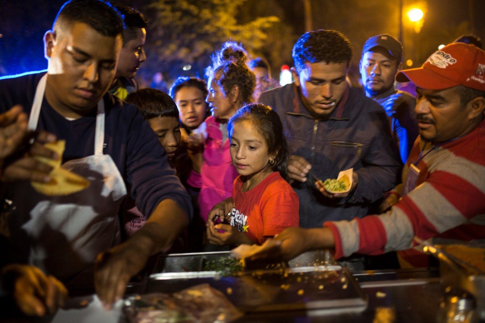 Мигранти от кервана получават храна от дарители в Мексикали, Мексико