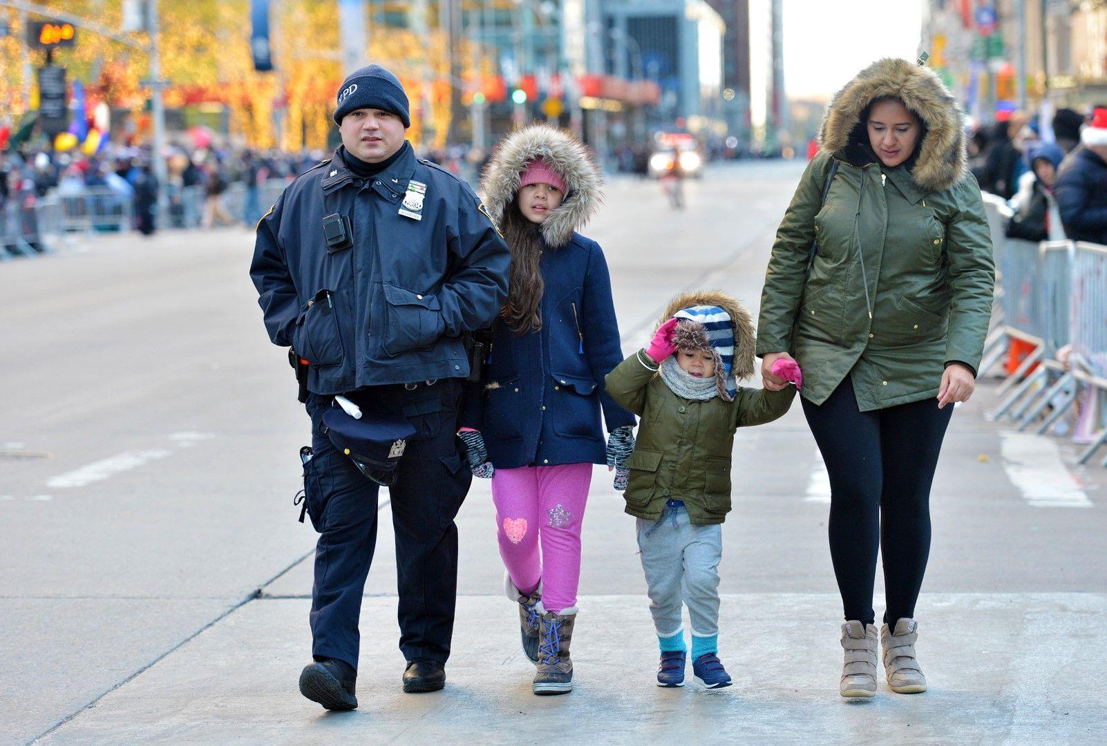Полицай съпровожда майка с двете й деца през улица със спряно движение
