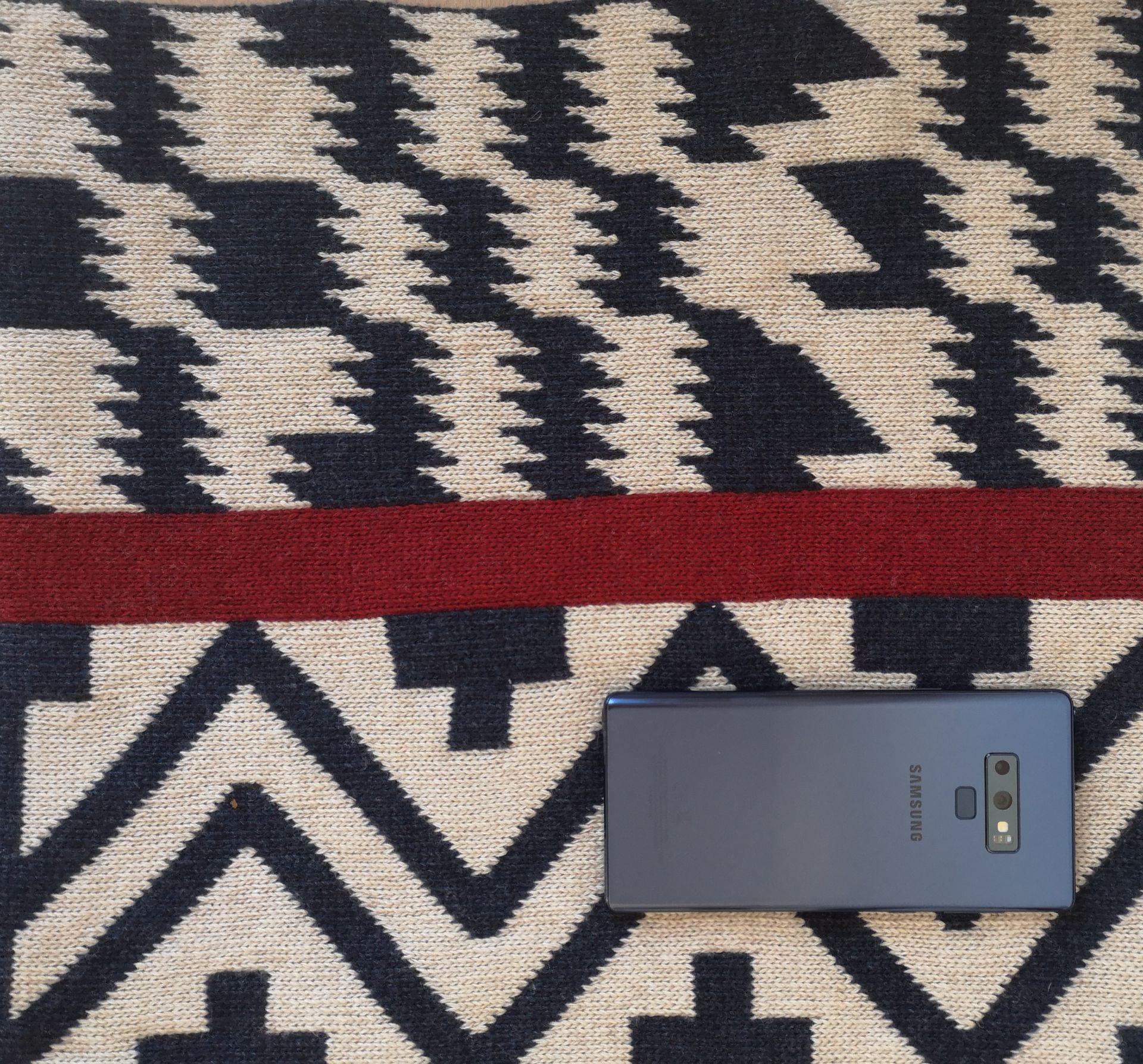 Топлият шал от зимната колекция на Шевица със сини мотиви чудесно си отива с  Samsung Galaxy Note9 в цвят морско синьо.