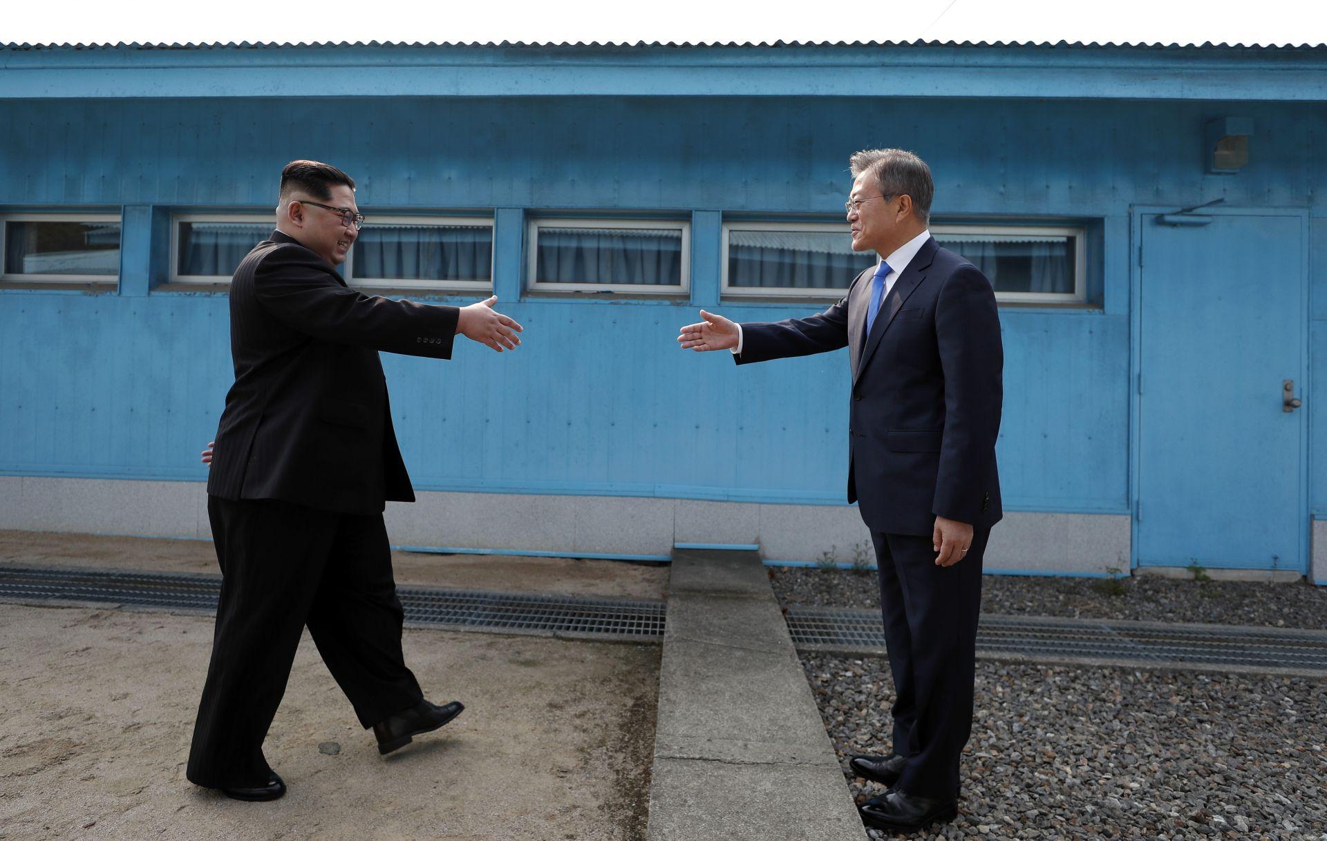 Лидерът на Северна Корея Ким Чен Ун (вляво) се ръкува с президента на Южна Корея Мун Дже-ин (вдясно) на линията, която разделя страните им преди срещата на върха в село Панминджон на 27 април