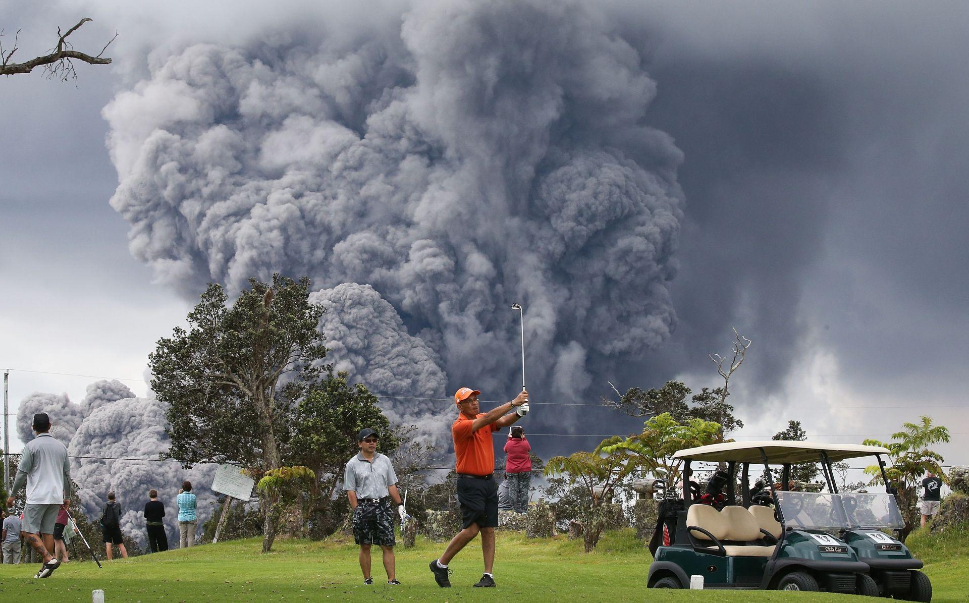 Игра на голф в Националния парк на Хаваите, а в далечината се вижда облак пепел, издигнат от вулкана Килауеа на 15 май в Националния парк Вулкани Хавай, Хавай на фона на облак пепел от вулкана Килауеа на Хаваите на 15 май