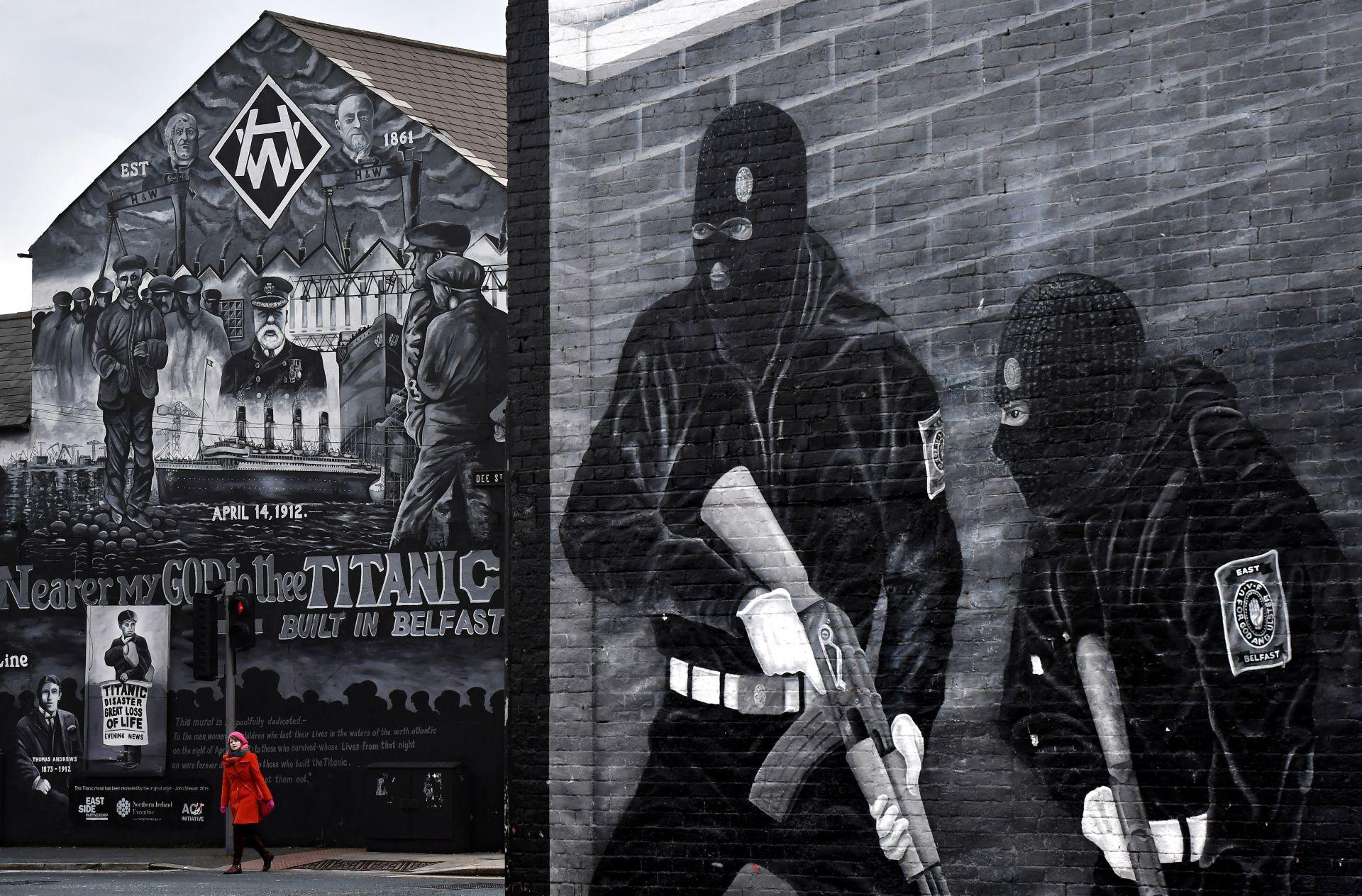 """На 1 март жена пресича улицата в Белфаст на фона на изрисуваната стена, посветена на загиналите на кораба """"Титаник"""". Стенописът обаче е засенчен от графит прославящ участниците в паравоенните отряди"""