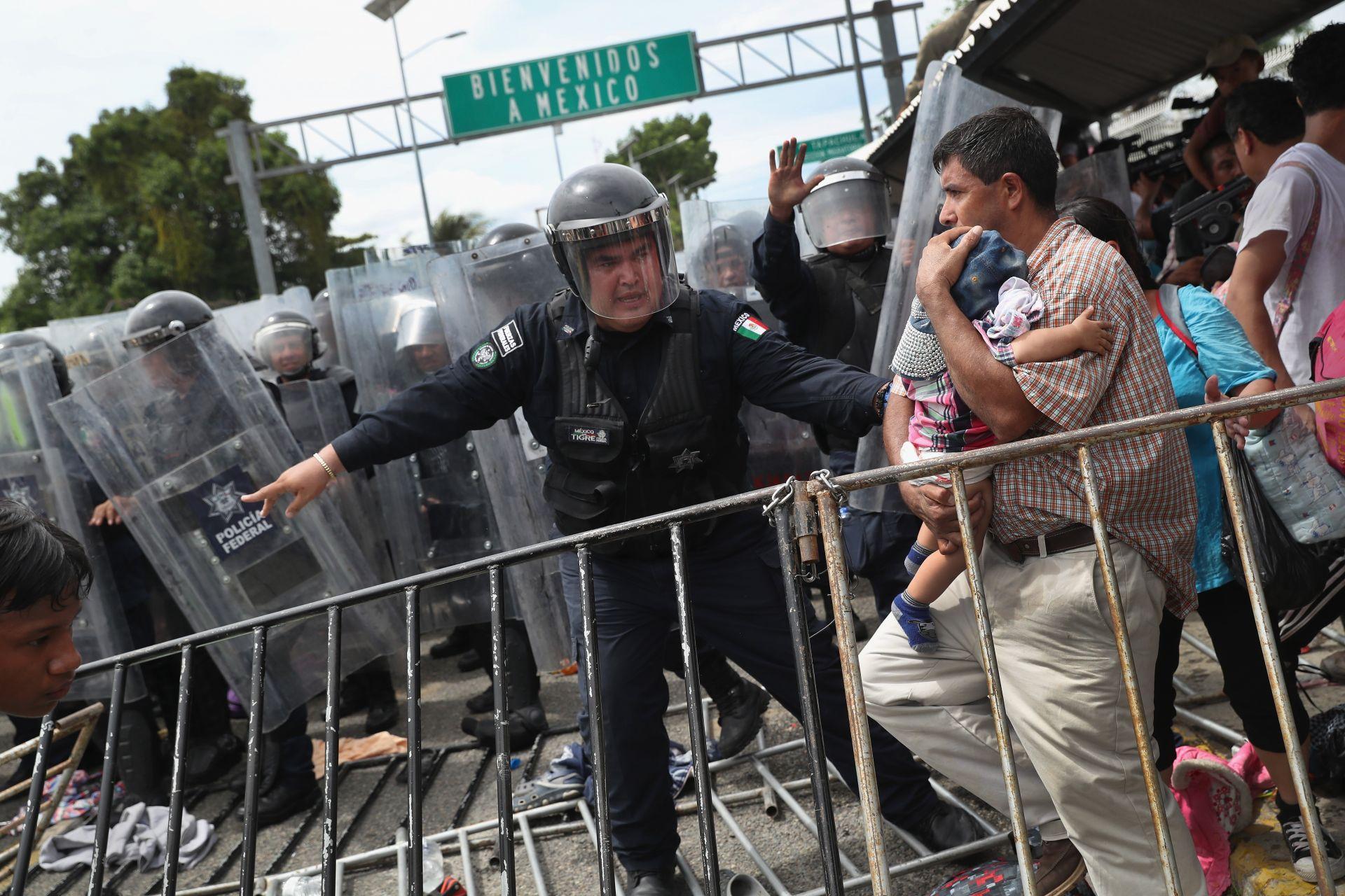 Мексикански полицай за борба с безредиците защитава мигрант с дете по време на сблъсъци между полицията и каравана с мигранти на границата между Мексико и Гватемала на 19 октомври