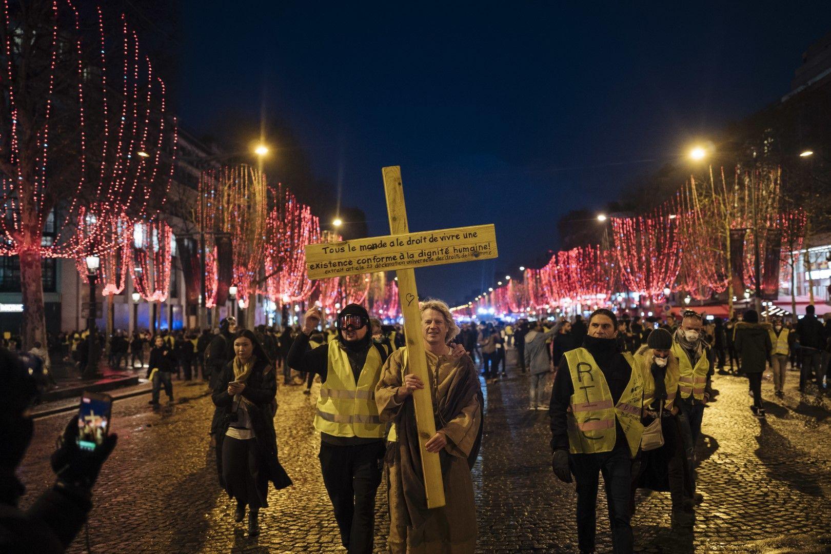 Оредял протест на жълти жилетки в събота, 22 декември 2018 г., в Париж. Демонстранти носят жълт кръст с изписан на него текст от Декларацията за правата на човека