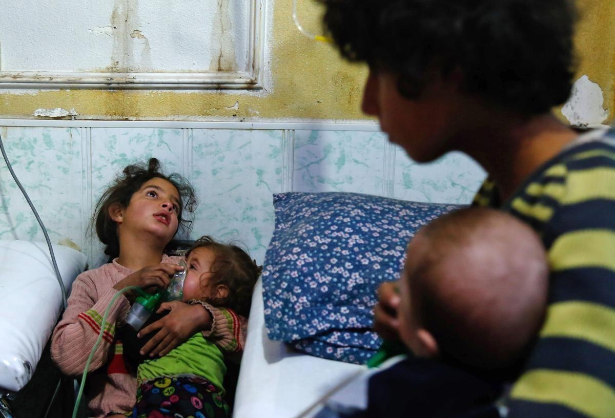 Сирийско момиче държи кислородна маска на дете в импровизирана болница след газовата атака в обсадения от бунтовници град Дума в източния регион Гута на 22 януари