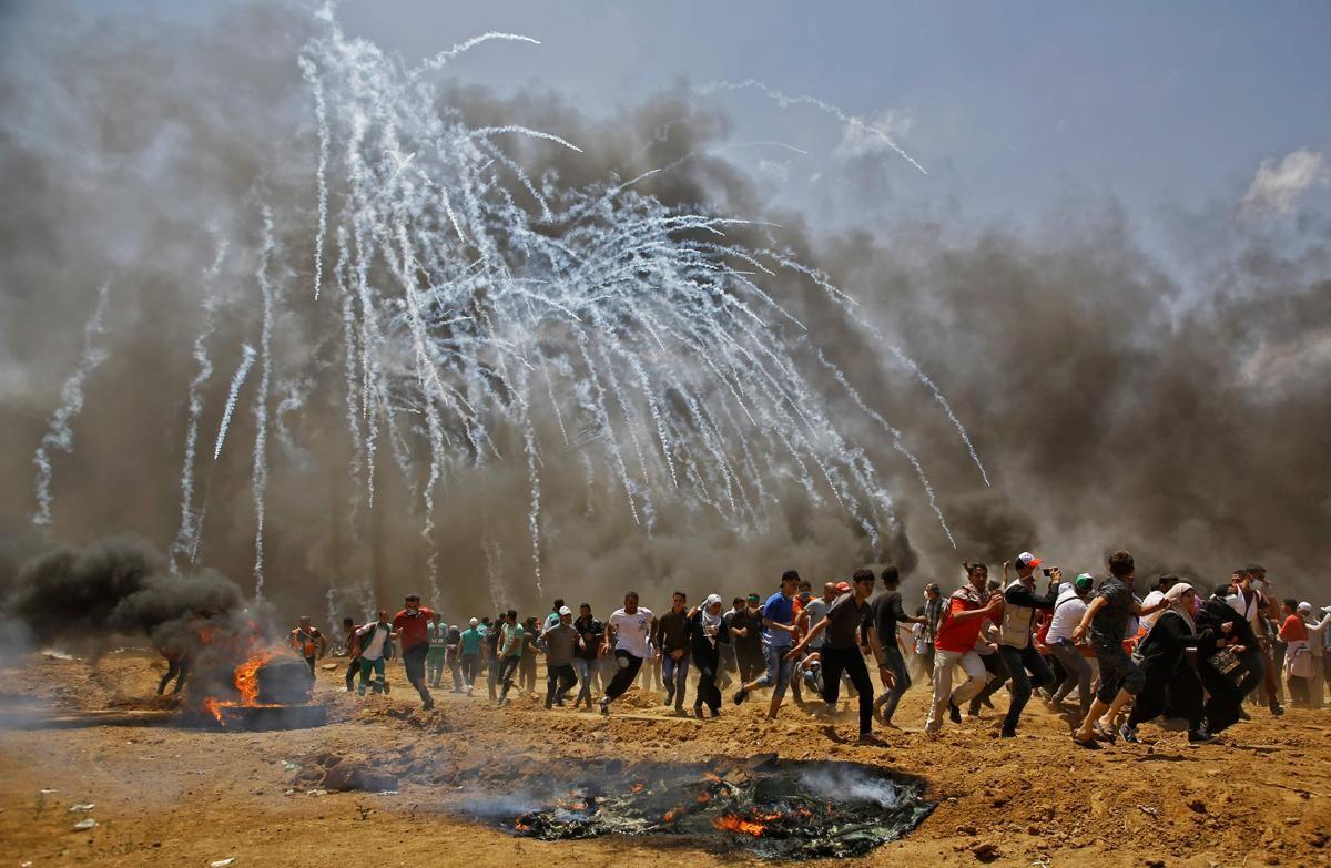 Палестинците бягат от сълзотворен газ по време на сблъсъци с израелските сили за сигурност в близост до границата между Израел и ивицата Газа на 14 май, когато протестираха срещу преместването на американското посолство в Йерусалим