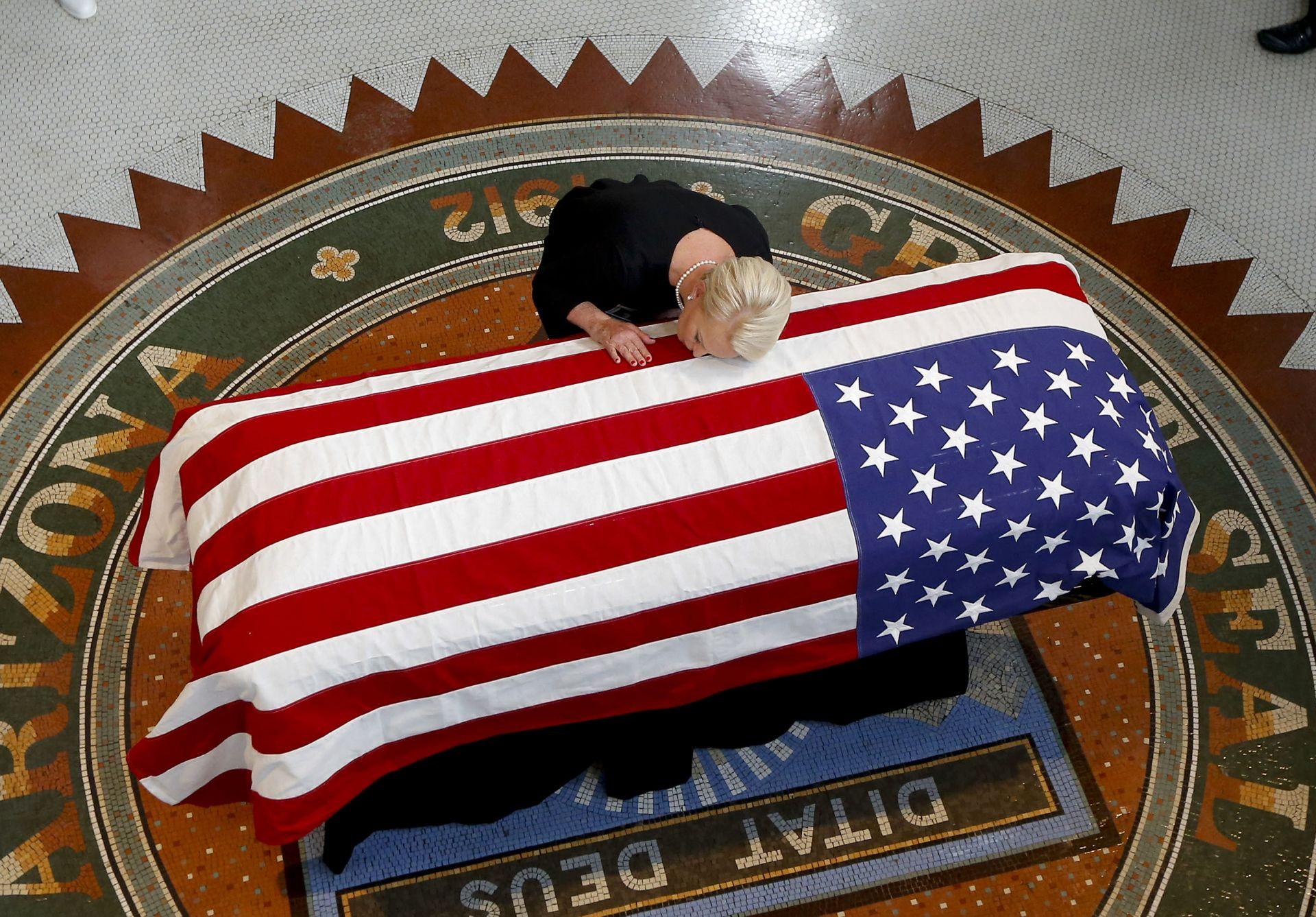 Съпругата на а сенатор Джон Маккейн полага глава върху ковчега му в Аризона на 29 август