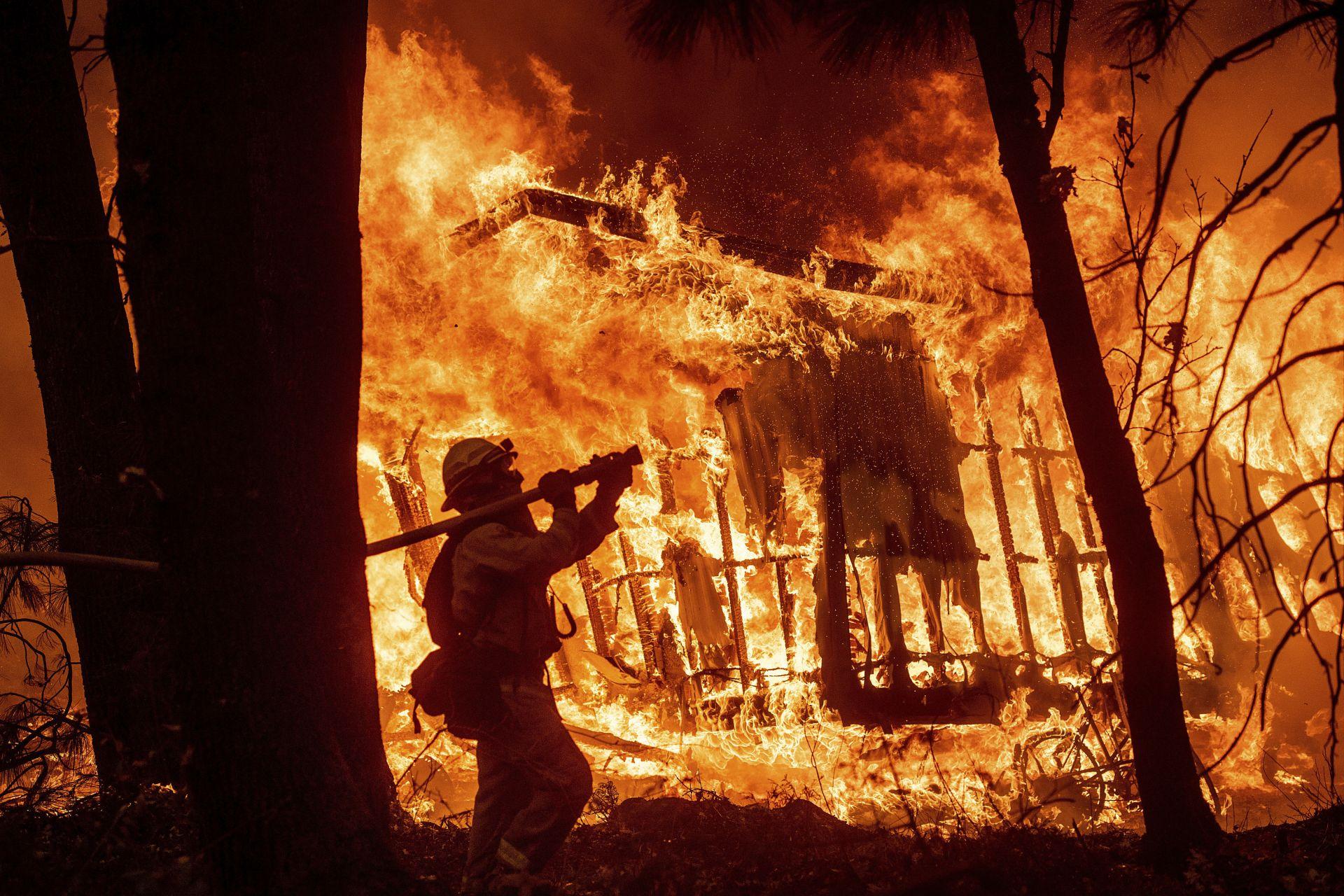 Пожарникар пред горящ дом в резултат на горските пожари в Калифорния