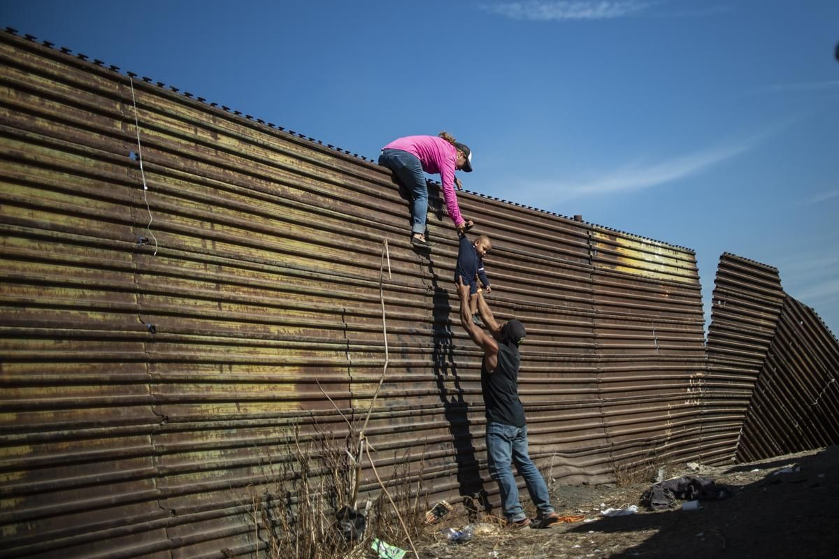 Семейство мигранти от Централна Америка се изкачват по границата между Мексико и Съединените щати, близо до граничния пункт Ел Чапарал, в Тихуана, 25 ноември