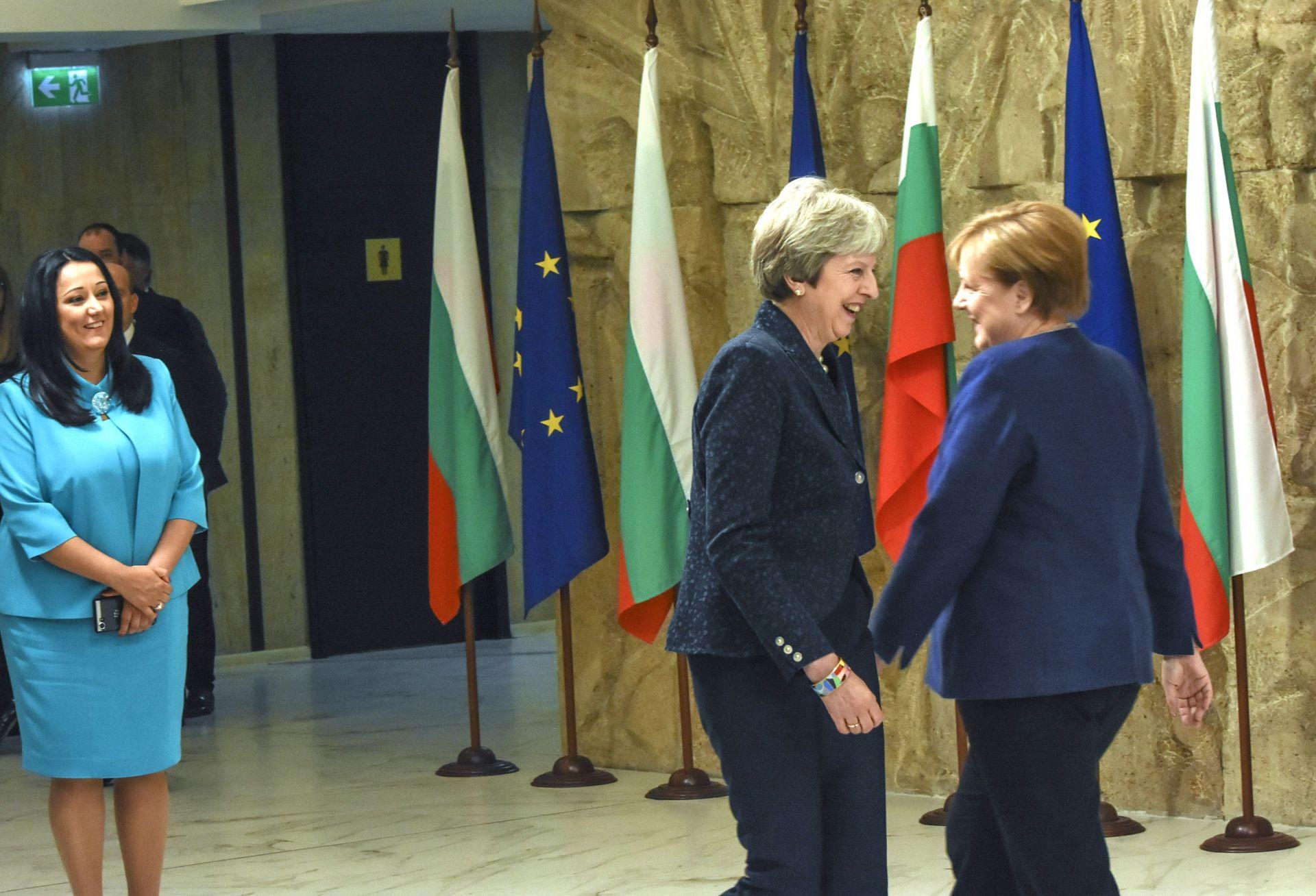 Знакова снимка, на която Ангела Меркел и Тереза Мей се разминават пред погледа на министърката на европредседателството Лиляна Павлова
