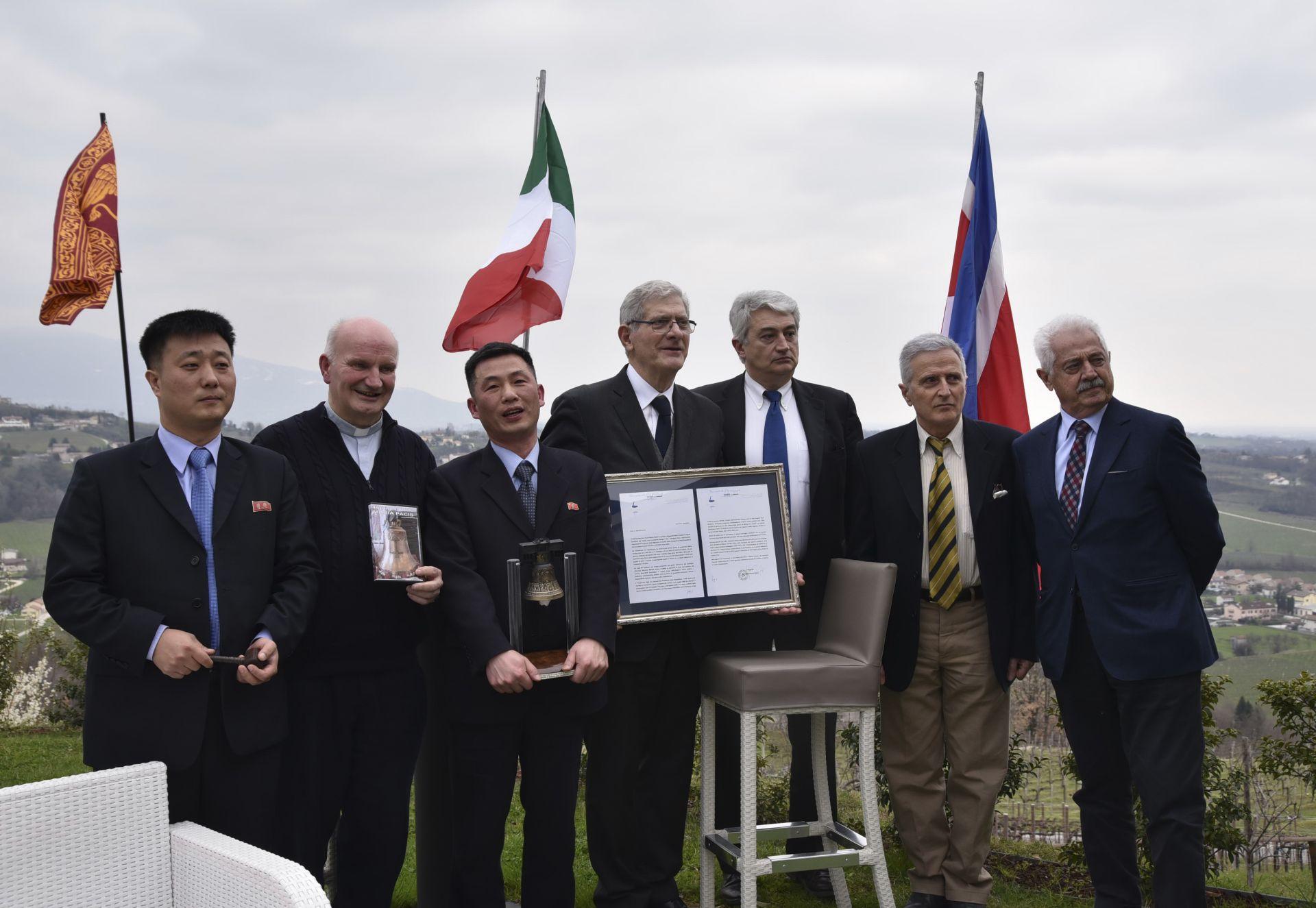 """Джо Сон-гил (в средата) държи """"Камбаната на мира от Роверето"""" по време на посещение на севернокорейска делегация в провинция Венето, в Сан Пиетро ди Фелето, близо до Тревизо, Северна Италия, 20 март 2018 г."""