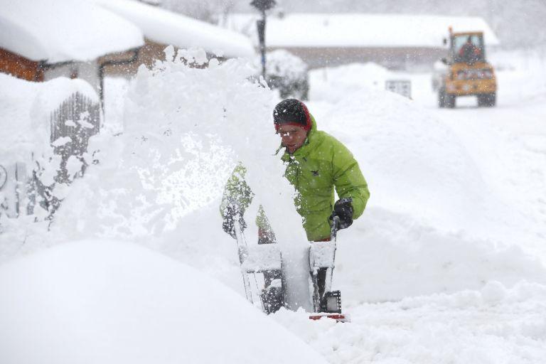 Човек използва снегорин след тежък снеговалеж около Иршенберг, южно от Мюнхен
