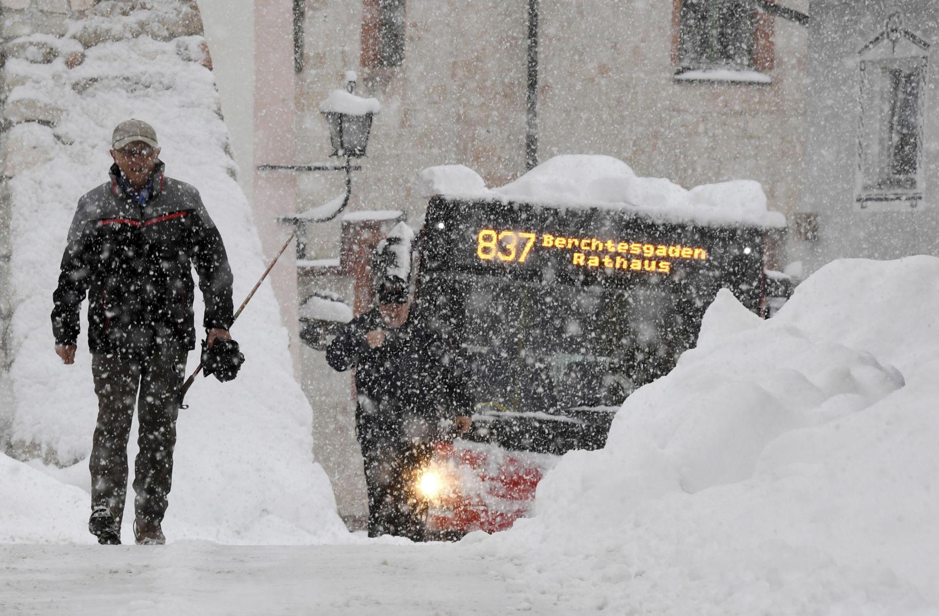 Човек и автобус си проправят път по улица в Берхтесгаден, южна Германия