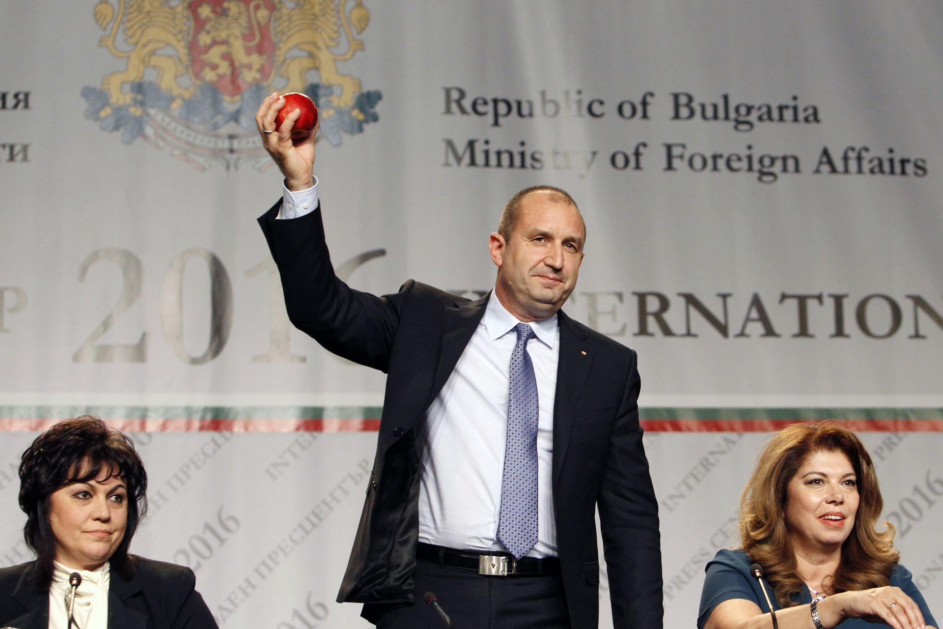 Румен Радев държи в ръката си току-що хвърлената от Беновска ябълка