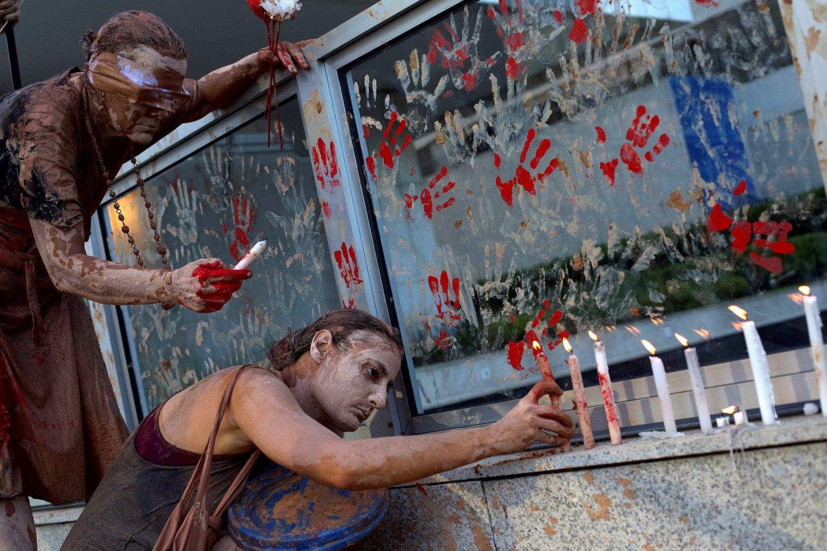 Жени, покрити с кал, палят свещи в памет на загиналите