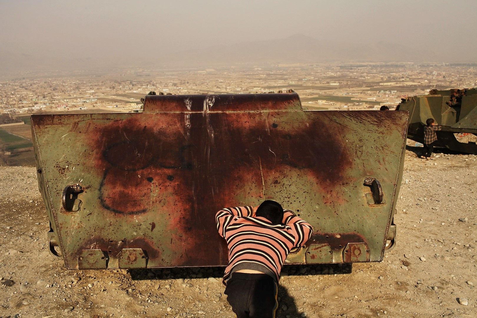Деца играят на криеница сред останки от съветски бойни машини на хълм над Кабул