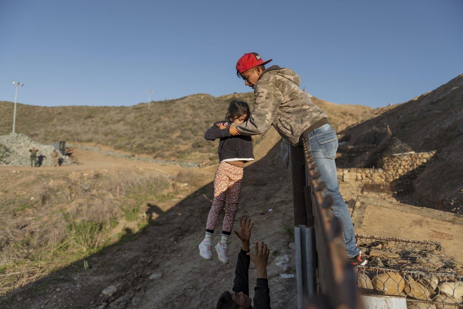 Мигранти от Хондурас преминават през оградата по границата между САЩ и Мексико при Сан Диего, Калифорния