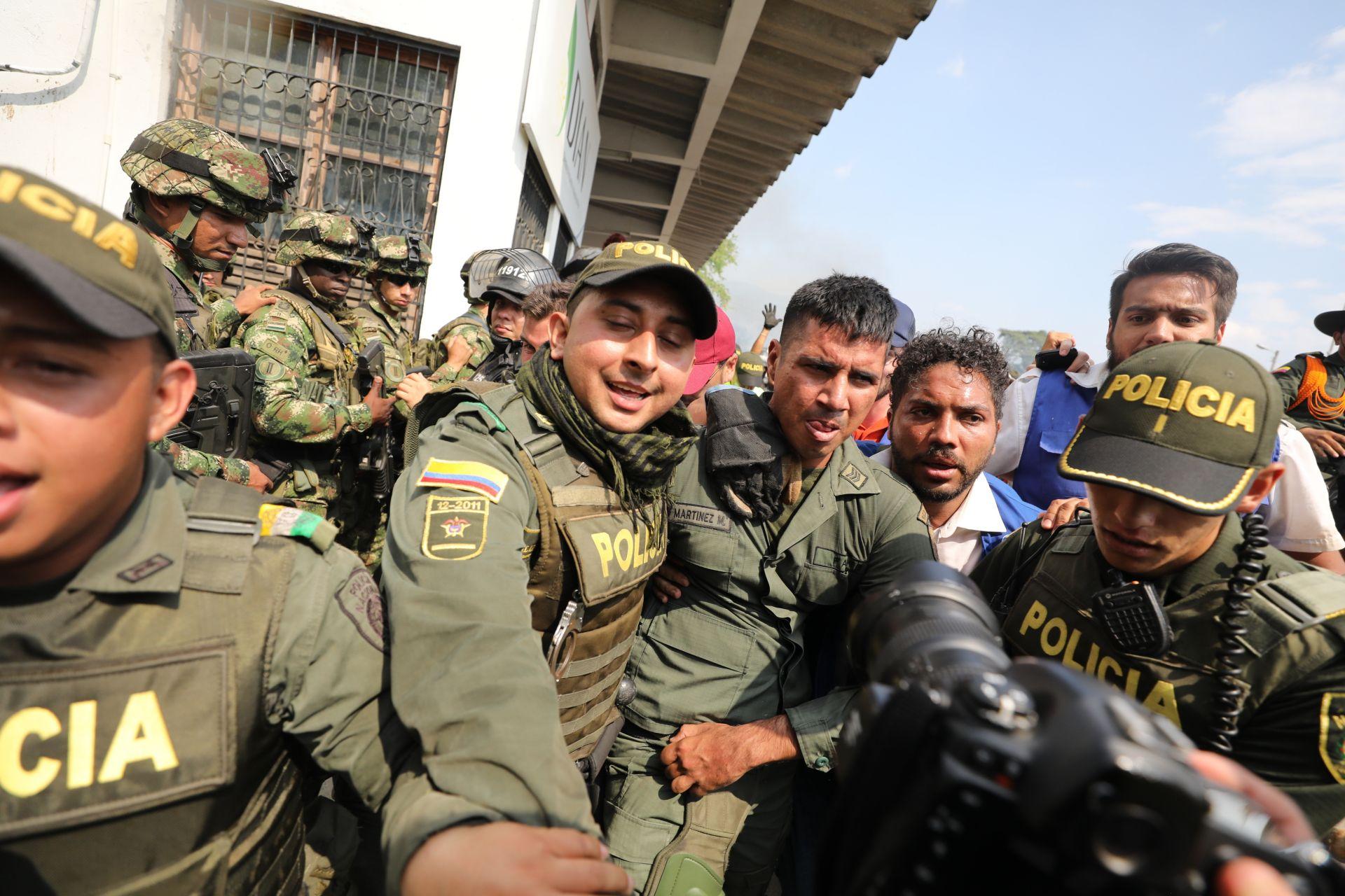 Колумбийски полиции ескортират венецуелски войник, който се предаде на международния мост Симон Боливар, където венецуелците се опитват да доставят хуманитарна помощ