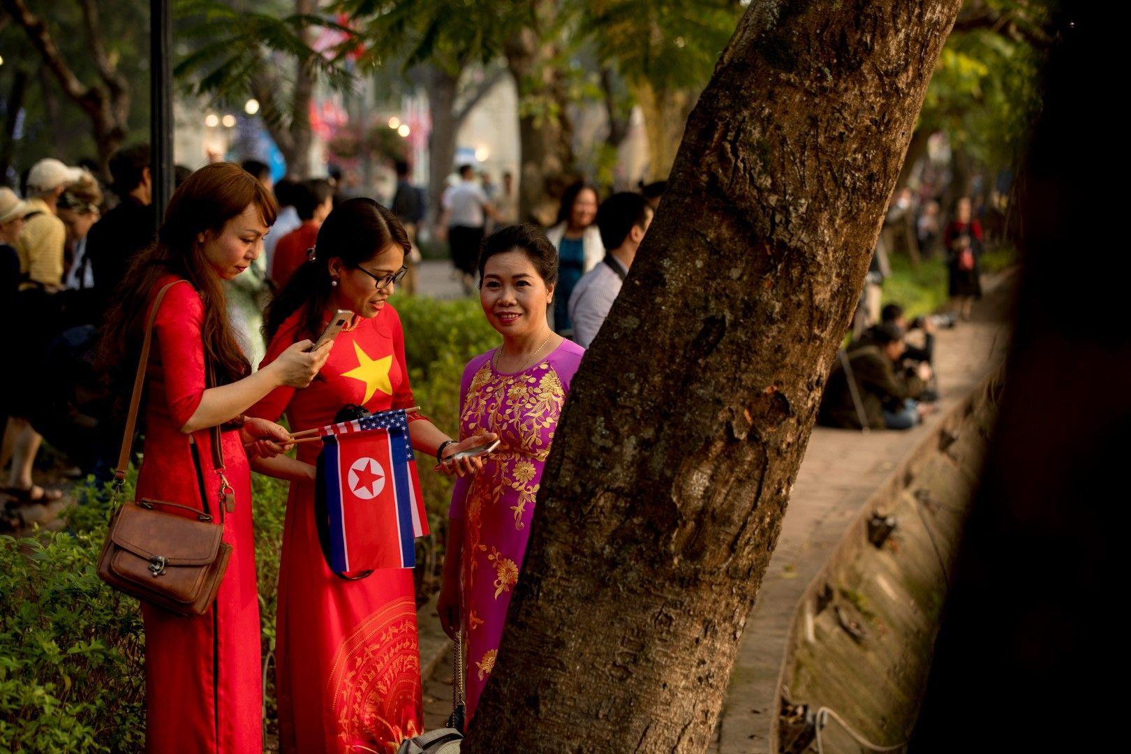 Виетнамски жени очакват Ким и Тръмп с националните флагове на Северна Корея и САЩ