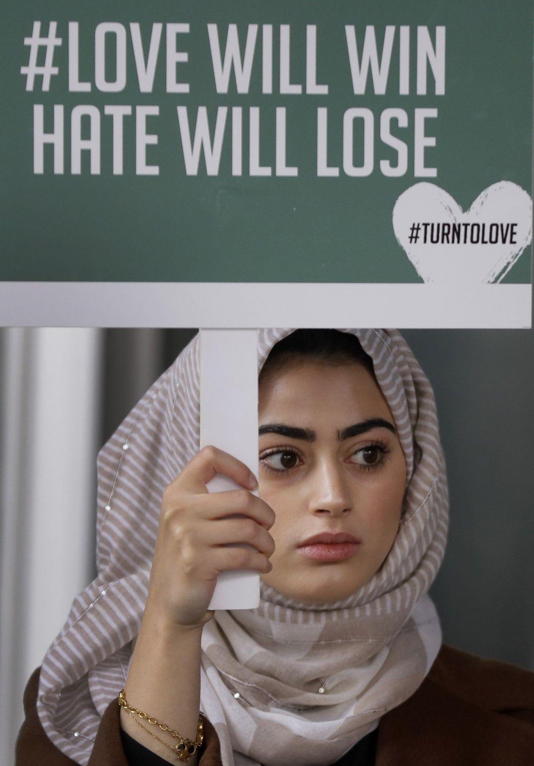 """Демонстрантка в Лондон държи плакат, на който пише: """"Любовта ще победи, омразата ще загуби"""""""