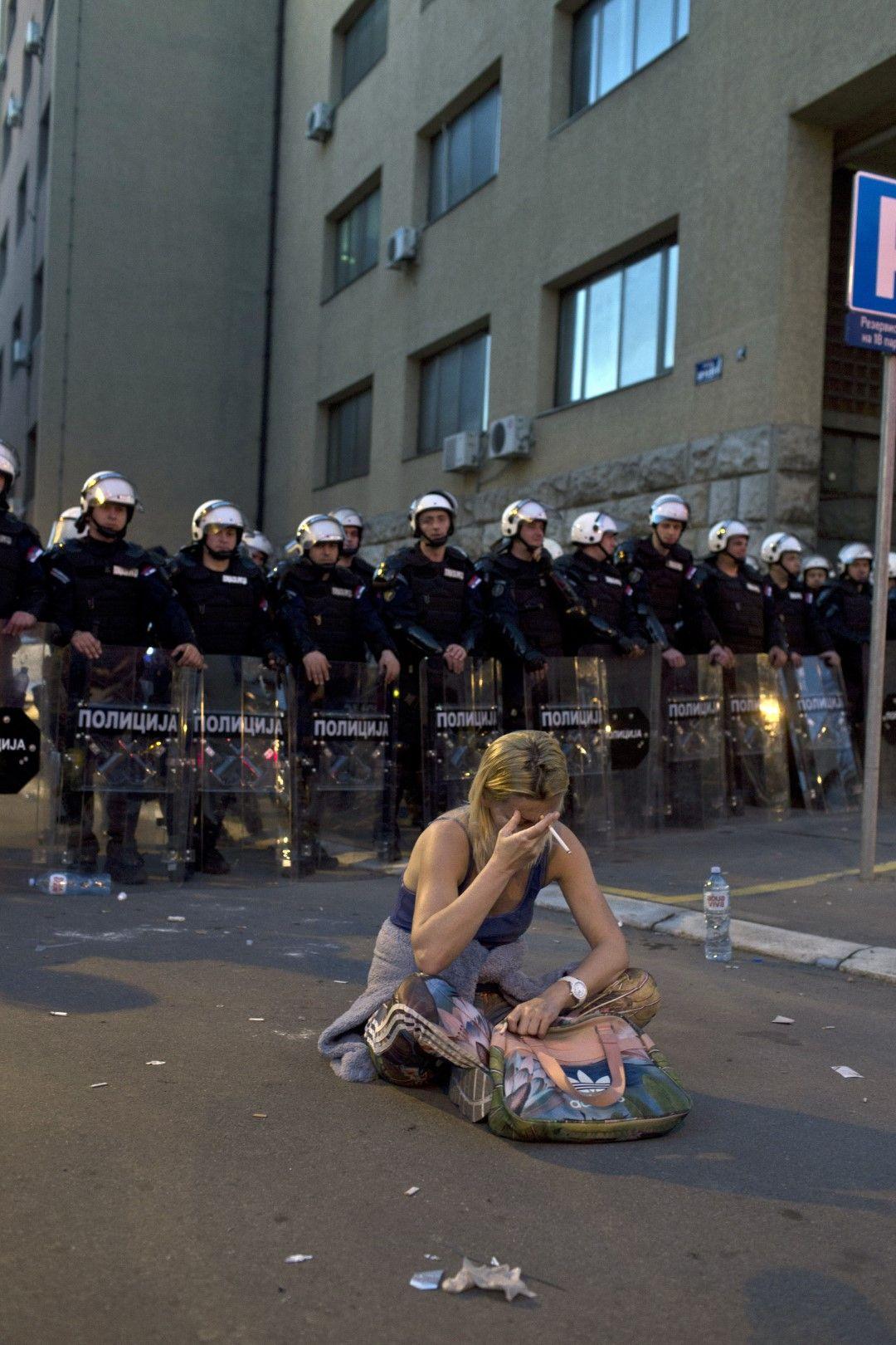Жена стои с цигара в ръка пред полицейски кордон в неделния протест в Белград