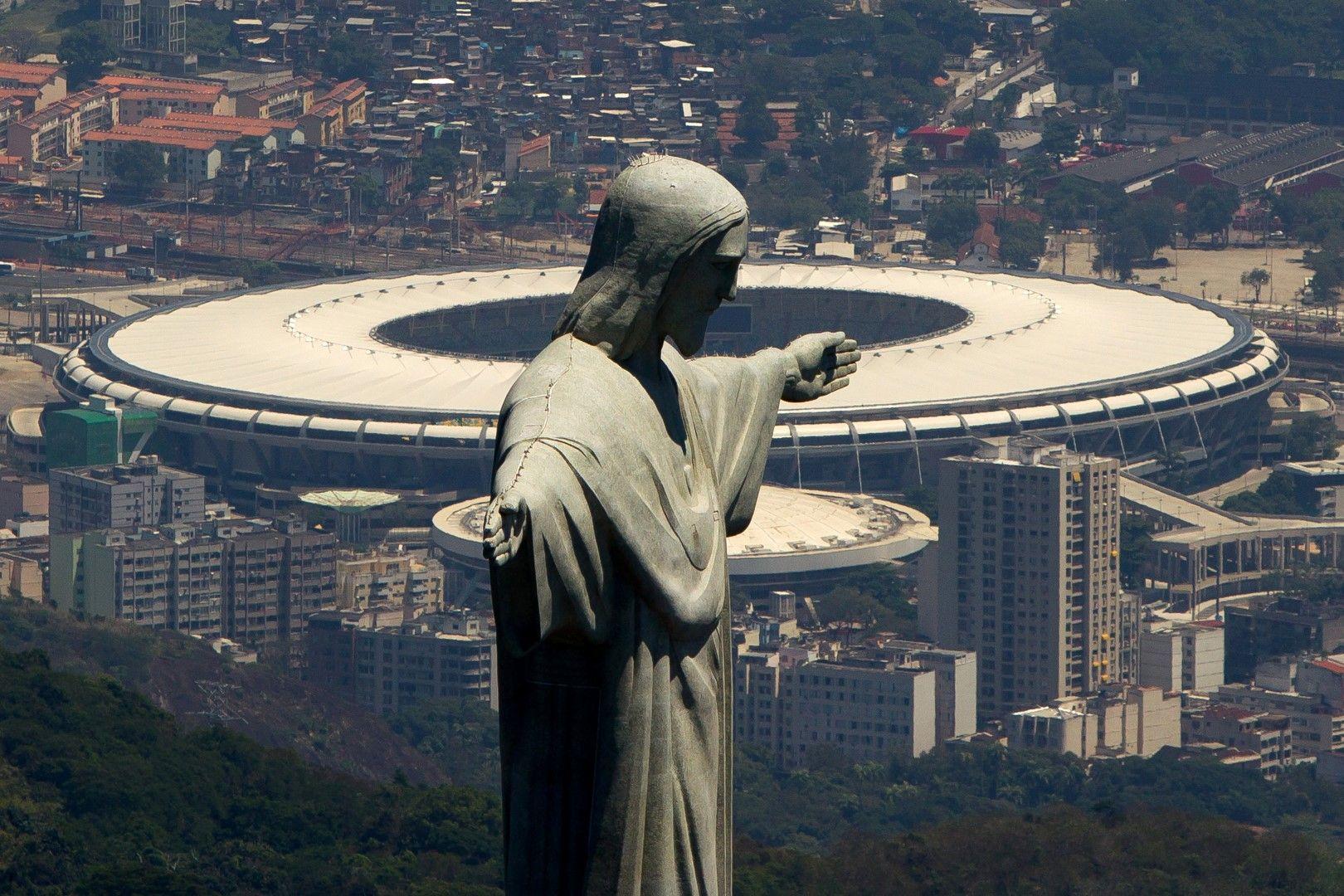 """Статуята на Исус Христос на фона на """"Маракана"""" е една от най-красивите футболни гледки дори и да не сте религиозни. Няма как да я пропуснем. Историческият футболен дом на Рио Де Жанейро се ползва от Фламенго, Флуминензе и националния отбор. Събира 79 хиляди души, а първите събития на него са през 1950-а година. Приемал е финалите на Световно първенство по футбол (1950-а и 2014-а), както и Олимпиадата през 2016-а."""
