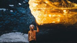 Фотограф улавя невероятно кехлибарено сияние в ледените пещери на Исландия