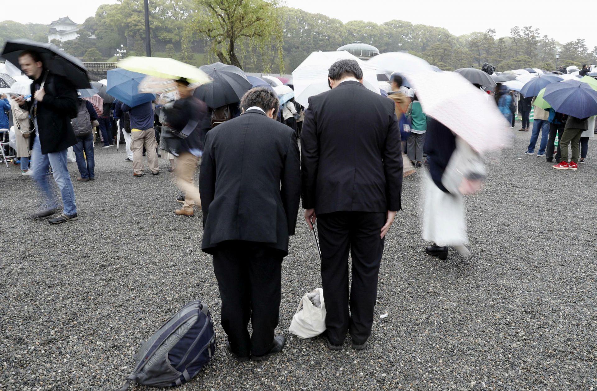 Хората се покланят към императорския дворец по време на церемонията по абдикацията на император Акихито