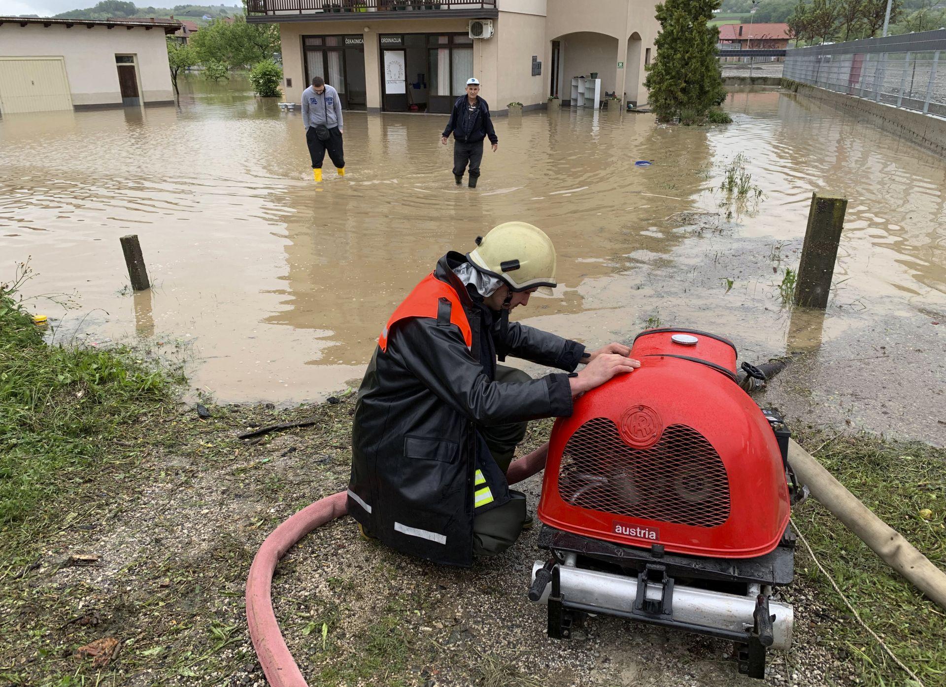 Пожарникар изпомпва водата от наводнен дом в Босна