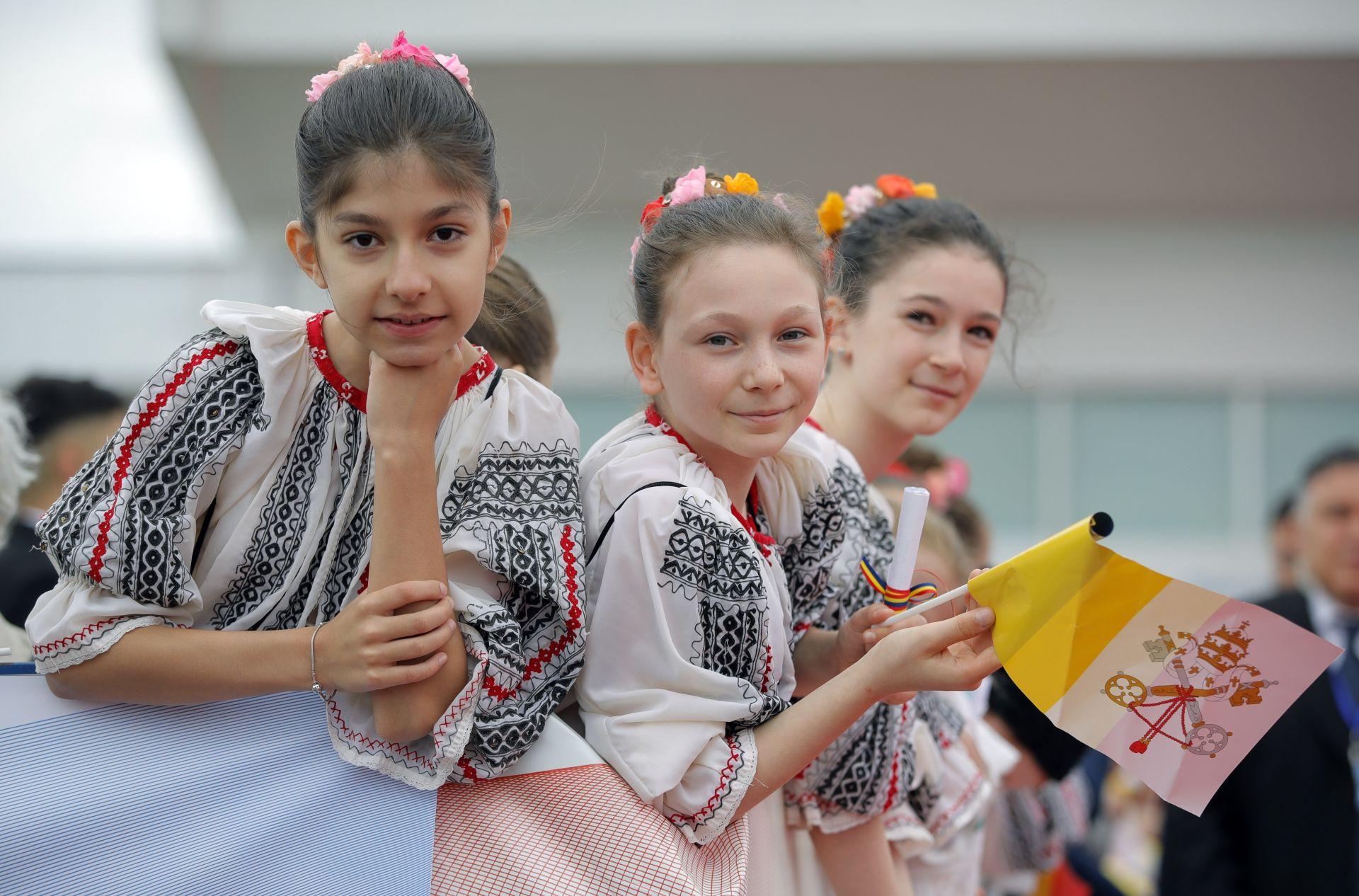 Млади момичета, облечени в румънски народни носии посрещат папата на летището