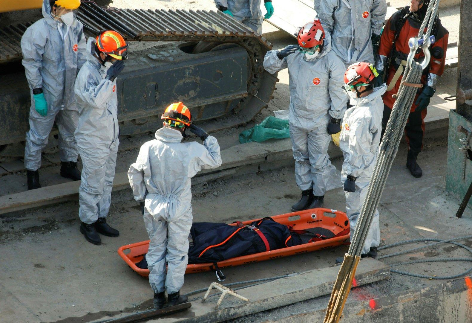 Спасителен екип отдава почит пред едно от извадените тела