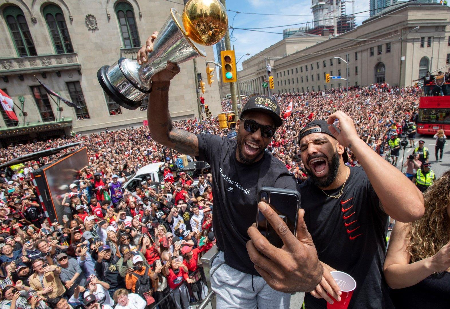 Звездата на Торонто Раптърс Кауай Леонард държи купата, до него е рапърът Дрейк, а зад тях е многолюдната тълпа преди да проехтят изстрелитее