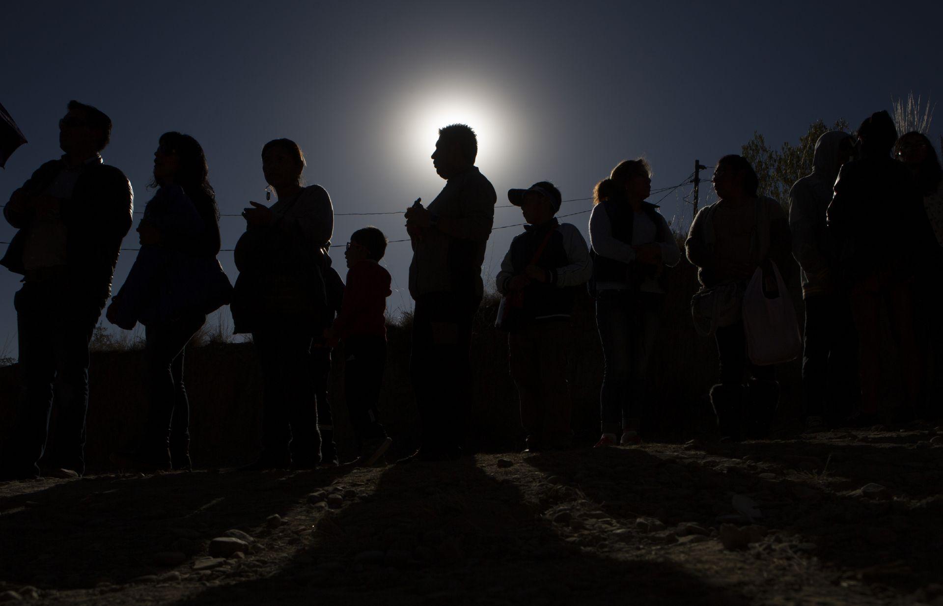 Хора стоят на опашката за да видят слънчевото затъмнение чрез телескоп в астрономически комплекс в Ла Пас, Боливия
