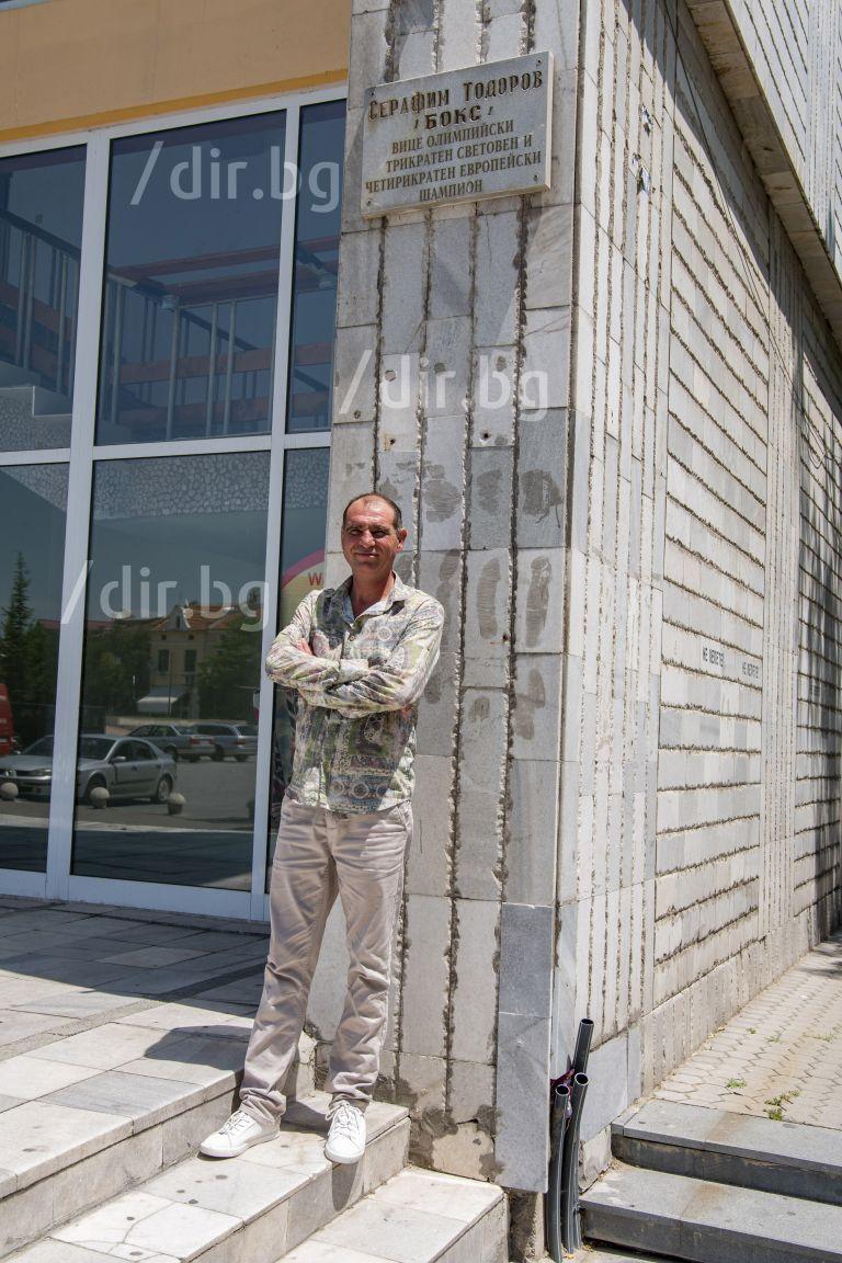 """Сарафа пред плочата на славата с неговото име, поставена пред входа на голямата спортна зала в Пазарджик - """"Христо Ботев"""""""